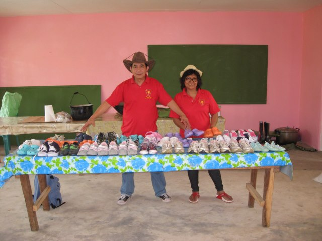 Mr. & Mrs. Digay with the table full of brand new shoes for the children